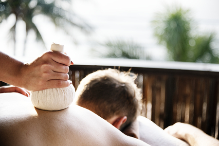 Man having an herbal compress massage at a spa Stock Photo