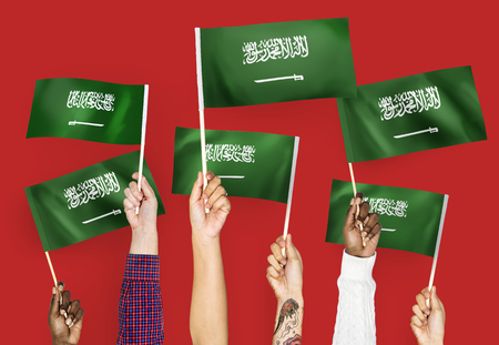 Hands waving the flags of Saudi Arabia Stock Photo