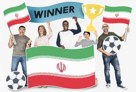 Diverse football fans holding the flag of Iran 스톡 콘텐츠