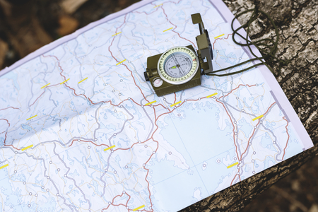 Map and compass on tree trunk Stock Photo