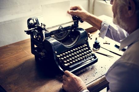 Closeup of hands changing paper on vintage typewriter
