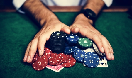 Closeup of hands with gambling tokens and card 写真素材 - 105411392