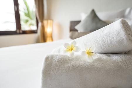 Zwinięte czyste ręczniki na łóżku