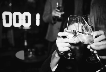 People toasting with a glass of champagne in a NYE party Stock Photo