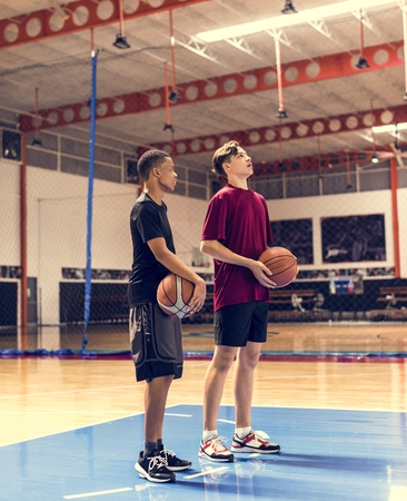 Teenage boys holding basketball on the court team and aspiration concept Stock Photo