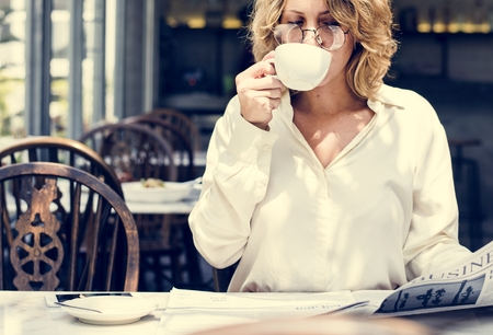 Business woman reading newspaper in the morning Stock Photo