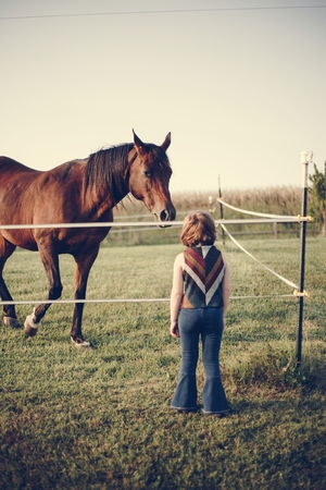 Young girl with a horse in the field Stock Photo
