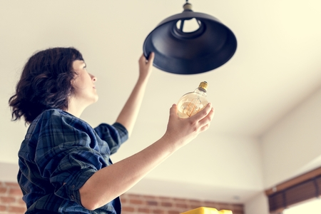 Woman changing lightbulb Banque d'images - 106300909