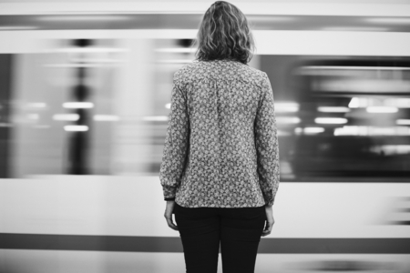 Rear view of a blond woman waiting at the train platform 스톡 콘텐츠
