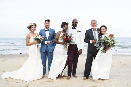 Three newly wed couples on the beach Stock fotó