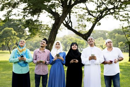Group of muslim people looking upward while holding mobile phones
