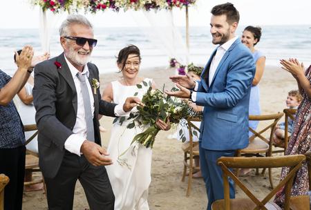 Jugendliches reifes Paar, das am Strand heiratet