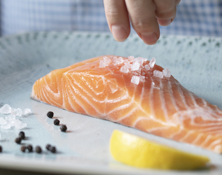 A person seasoning a fillet of salmon food photography recipe idea Standard-Bild