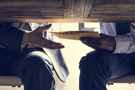 Gente de negocios enviando documentos debajo de la mesa.