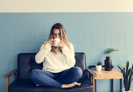 A Caucasian Woman Sitting and Drinking Coffee