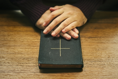 Hands over the bible on a wooden table