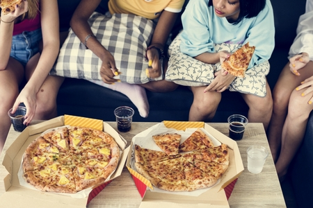 Diverse women sitting on the couch eating pizza together Stock Photo