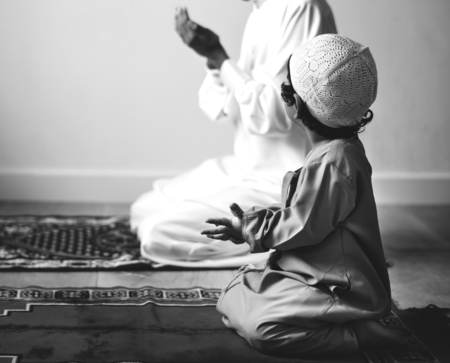 Muslim boy learning how to make Dua to Allah Stock Photo - 106352409