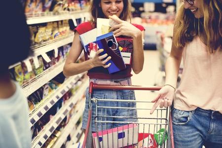 Women choosing food from a supermarket shelf Stock Photo