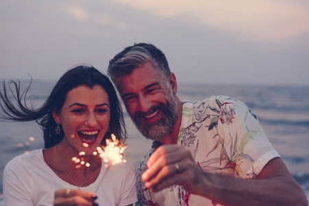 Couple celebrating with sparklers at the beach Stok Fotoğraf - 106354001