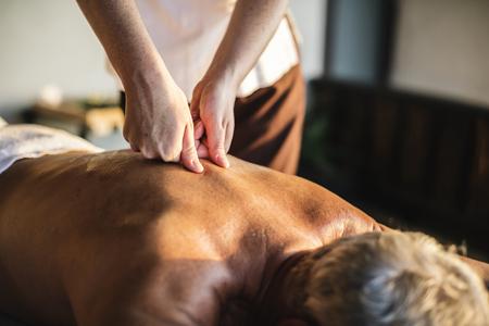 Vrouwelijke berichtentherapeut die een massage geeft in een spa Stockfoto