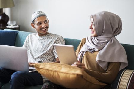 Muslimische Familie mit digitalen Geräten zu Hause Standard-Bild