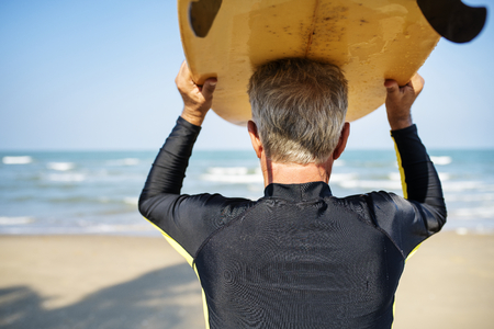 Mature surfer ready to catch a wave Stockfoto