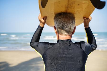 Surfista maduro listo para coger una ola Foto de archivo