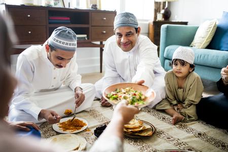 Muslim family having dinner on the floor Stock Photo