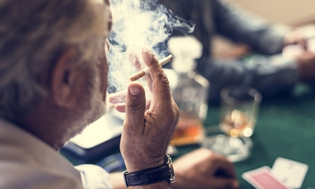 A man smoking in a gambling circle Stok Fotoğraf