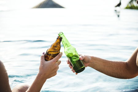 Young couple having a beer by the pool