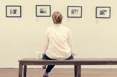 Woman looking at frames in an exhibition Reklamní fotografie