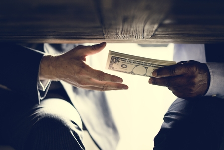 Hands passing money under table corruption bribery Archivio Fotografico