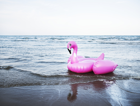 Inflatable pink flamingo tube on the beach Reklamní fotografie