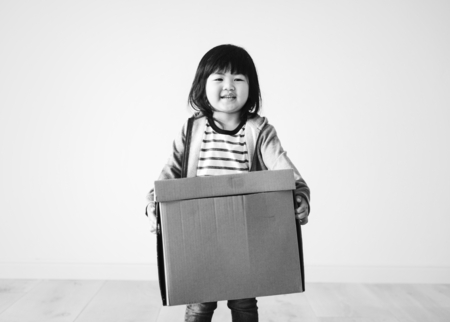 Asian kid helping to move to a new house