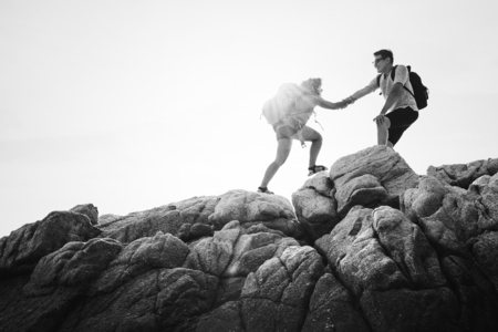 Friends helping each other up a mountain