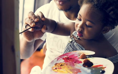African descent dad teaching his child how to paint Stockfoto