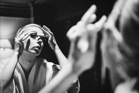 Drag queen make-up in een spiegel toe te passen