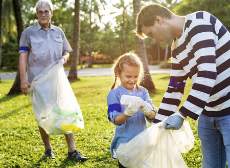 Kids picking up trash in the park Stock Photo