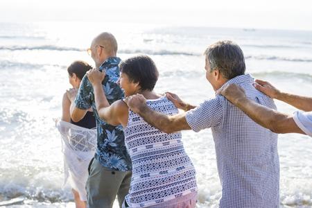 Senior friends playing at the beach Standard-Bild - 106369443