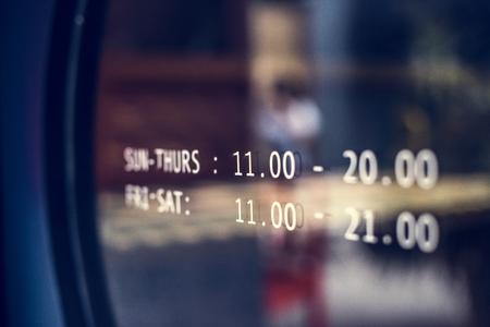 Ankündigung der Geschäftszeiten an einem Fenster