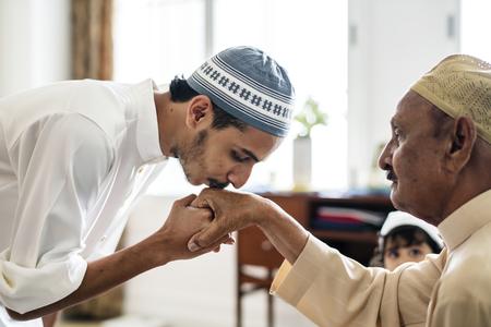 Junger muslimischer Mann, der Respekt vor seinem Vater zeigt