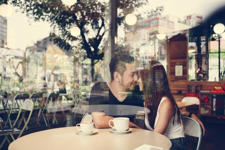 Lovely asian couple having coffee Фото со стока - 106374710