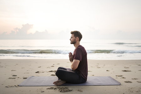Man practicing yoga on the beach Standard-Bild