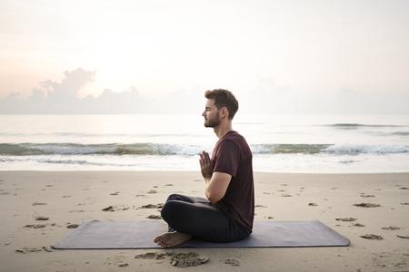 Mann, der Yoga am Strand praktiziert