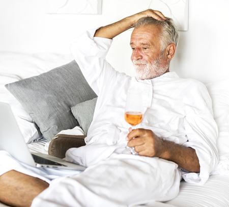 Senior man having prosecco in bed