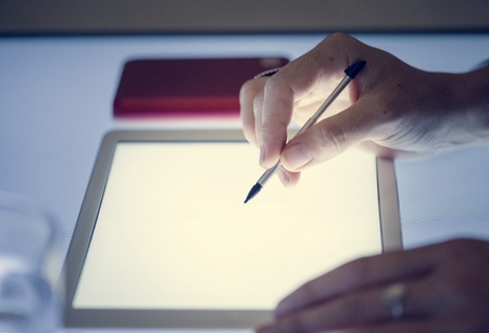 Hand using magic pen on a tablet screen Stock Photo