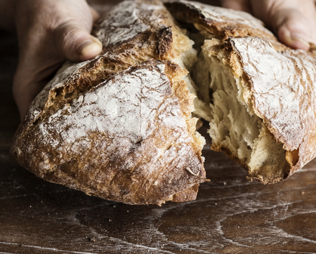 Tearing a bread loaf photography recipe idea Stock Photo