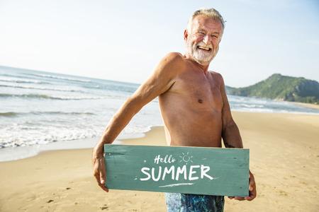 Senior man holding a signboard at the beach