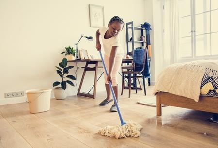 Young teen girl sweeping up the floor Stock Photo